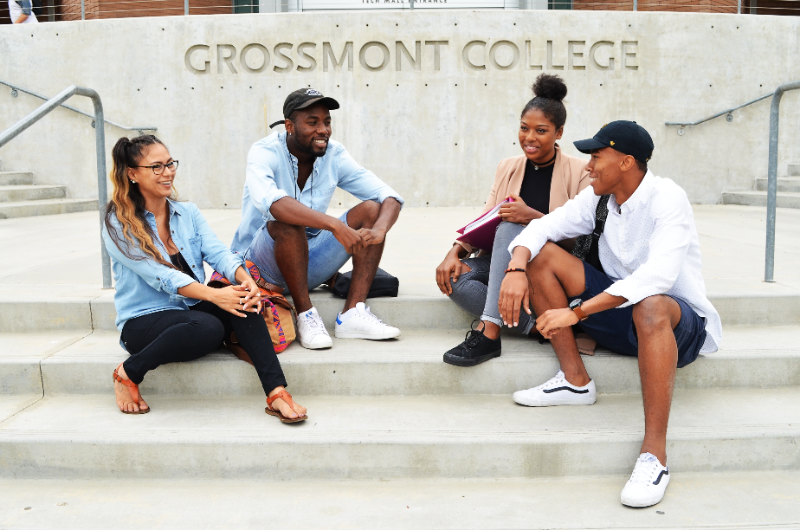 group of students sitting in front of a building outside